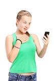 Έκπληκτο κορίτσι που εξετάζει ένα τηλέφωνο κυττάρων στοκ φωτογραφία