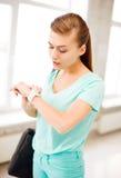 Έκπληκτο κορίτσι σπουδαστών που εξετάζει το wristwatch στοκ φωτογραφία