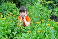 Έκπληκτο μικρό κορίτσι μεταξύ των λουλουδιών του calendula Στοκ Φωτογραφία