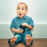 Έκπληκτο μικρό παιδί με ένα τηλέφωνο κυττάρων στοκ εικόνα
