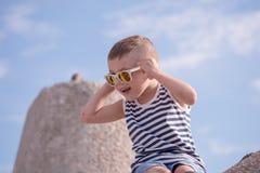 Έκπληκτο μικρό παιδί με το πουκάμισο γυαλιών ηλίου και λωρίδων ναυτικών Στοκ Φωτογραφία