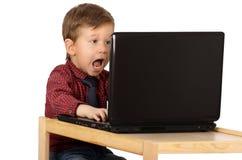 Έκπληκτο μικρό παιδί που εργάζεται σε έναν φορητό προσωπικό υπολογιστή Στοκ εικόνα με δικαίωμα ελεύθερης χρήσης