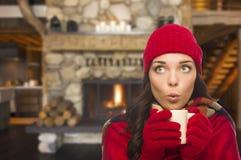 Έκπληκτο μικτό κορίτσι φυλών που απολαμβάνει τη θερμή κούπα εστιών και εκμετάλλευσης Στοκ Εικόνες