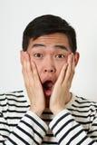 Έκπληκτο νέο ασιατικό άτομο που καλύπτει το πρόσωπό του με τους φοίνικες Στοκ Εικόνες