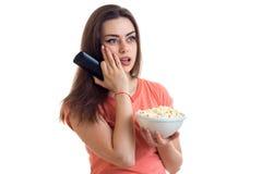Έκπληκτο νέο κορίτσι με pop-corn που προσέχει μια TV Στοκ Εικόνα