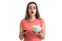 Έκπληκτο νέο κορίτσι που προσέχει μια TV με pop-corn Στοκ Εικόνες