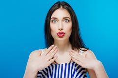 Έκπληκτο νέο όμορφο κορίτσι που εξετάζει τη κάμερα που απομονώνεται στο μπλε υπόβαθρο Στοκ εικόνες με δικαίωμα ελεύθερης χρήσης