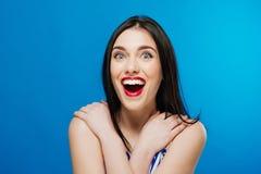 Έκπληκτο νέο όμορφο κορίτσι που εξετάζει τη κάμερα που απομονώνεται στο μπλε υπόβαθρο Στοκ φωτογραφία με δικαίωμα ελεύθερης χρήσης