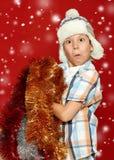 Έκπληκτο πορτρέτο παιδιών αγοριών στο καπέλο santa στο κόκκινο, που έχει τη διασκέδαση και τις συγκινήσεις, έννοια χειμερινών δια Στοκ Φωτογραφίες