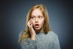 Έκπληκτο χαριτωμένο κορίτσι με το τηλέφωνο κυττάρων Απομονωμένος σε γκρίζο Στοκ Εικόνες