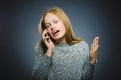 Έκπληκτο χαριτωμένο κορίτσι με το τηλέφωνο κυττάρων Απομονωμένος σε γκρίζο Στοκ Φωτογραφία