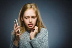 Έκπληκτο χαριτωμένο κορίτσι με το τηλέφωνο κυττάρων Απομονωμένος σε γκρίζο Στοκ εικόνες με δικαίωμα ελεύθερης χρήσης