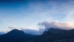 Έκρηξη σύννεφων πετάγματος στις κορυφές των βουνών ενάντια στο χρονικό σφάλμα μπλε ουρανού απόθεμα βίντεο