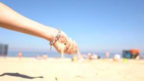 Έκχυση άμμου από τα χέρια μιας γυναίκας στην παραλία φιλμ μικρού μήκους