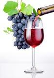 Έκχυση ενός ποτηριού του κόκκινου κρασιού και της δέσμης των σταφυλιών με τα φύλλα Στοκ φωτογραφίες με δικαίωμα ελεύθερης χρήσης