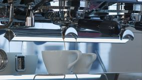 Έκχυση καφέ στα άσπρα κεραμικά φλυτζάνια από τη μηχανή καφέ Στοκ Εικόνες