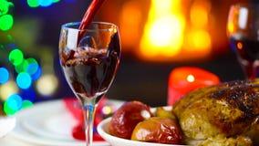 Έκχυση κρασιού στο γυαλί στον πίνακα Χριστουγέννων μπροστά από την εστία απόθεμα βίντεο