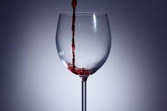Έκχυση κόκκινου κρασιού σε ένα γυαλί με το α με το υπόβαθρο στοκ φωτογραφίες