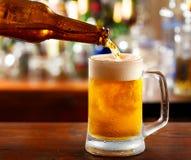 Έκχυση μπύρας στην κούπα Στοκ Εικόνες