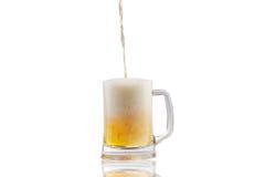 Έκχυση μπύρας στο κατά το ήμισυ πλήρες γυαλί πέρα από το άσπρο υπόβαθρο Στοκ Εικόνες