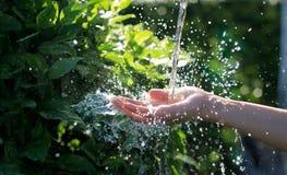Έκχυση νερού στο ανθρώπινο χέρι στη φύση, ζήτημα περιβάλλοντος στοκ φωτογραφία με δικαίωμα ελεύθερης χρήσης