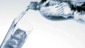 Έκχυση νερού στο γυαλί με τη χαμηλή άποψη γωνίας πάγου φιλμ μικρού μήκους