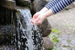 Έκχυση νερού στο χέρι γυναικών Στοκ Εικόνα