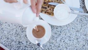 Έκχυση της καυτής σοκολάτας από teapot στο φλυτζάνι για το πρόγευμα φιλμ μικρού μήκους
