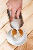 Έκχυση του αφρισμένου γάλακτος σε ένα φλιτζάνι του καφέ, δημιουργία σχεδίων Στοκ Φωτογραφία