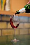 Έκχυση του κόκκινου κρασιού στο γυαλί στο φραγμό στοκ φωτογραφία με δικαίωμα ελεύθερης χρήσης