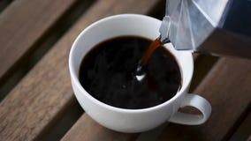 Έκχυση του μαύρου καφέ στο φλυτζάνι καφέ φιλμ μικρού μήκους