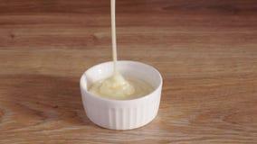 Έκχυση του συμπυκνωμένου γάλακτος στο άσπρο κύπελλο στον πίνακα απόθεμα βίντεο