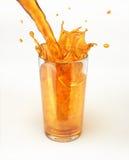 Έκχυση χυμού από πορτοκάλι σε ένα γυαλί, που διαμορφώνει έναν παφλασμό. Στοκ Φωτογραφία