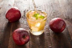 Έκχυση χυμού της Apple από τα κόκκινα φρούτα μήλων σε ένα γυαλί Στοκ Εικόνες
