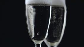 Έκχυση CHAMPAGNE από το μπουκάλι σε δύο γυαλιά στο μαύρο υπόβαθρο κλείστε επάνω απόθεμα βίντεο