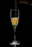 Έκχυση CHAMPAGNE στο γυαλί από το μπουκάλι που απομονώνεται στο μαύρο backgro Στοκ εικόνα με δικαίωμα ελεύθερης χρήσης