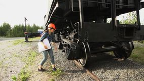 Έλεγχοι νέοι γυναικών railroader του άξονας-κιβωτίου του βαγονιού εμπορευμάτων φορτίου απόθεμα βίντεο