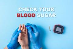 Έλεγχος επιγραφής η ζάχαρη αίματός σας, νοσοκόμα που κάνει μια εξέταση αίματος με το νυστέρι Χέρι ατόμων ` s, κόκκινη πτώση αίματ στοκ εικόνα με δικαίωμα ελεύθερης χρήσης