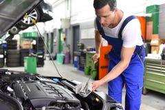 Έλεγχος επιπέδων πετρελαίου της μηχανής αυτοκινήτων από τους μηχανικούς σε ένα αυτοκίνητο worksh Στοκ φωτογραφία με δικαίωμα ελεύθερης χρήσης