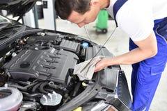 Έλεγχος επιπέδων πετρελαίου της μηχανής αυτοκινήτων από τους μηχανικούς σε ένα αυτοκίνητο worksh Στοκ φωτογραφίες με δικαίωμα ελεύθερης χρήσης
