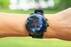 Έλεγχος του ποσοστού καρδιών από Amazfit το έξυπνο ρολόι stratos στο δημόσιο πάρκο στοκ φωτογραφίες