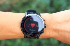 Έλεγχος του ποσοστού καρδιών από Amazfit το έξυπνο ρολόι stratos στο δημόσιο πάρκο στοκ εικόνα
