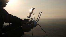 Έλεγχος χεριών του πετάγματος copter στην κινηματογράφηση σε πρώτο πλάνο ηλιοβασιλέματος φιλμ μικρού μήκους