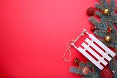 Έλκηθρο παιχνιδιών Χριστουγέννων με fir-tree τον κλάδο σε ένα κόκκινο υπόβαθρο στοκ φωτογραφία με δικαίωμα ελεύθερης χρήσης