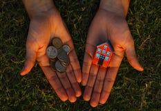 Έλλειψη χρημάτων για να αγοράσει μια έννοια σπιτιών Το άτομο κρατά το σπίτι παιχνιδιών σε μια χέρι και χούφτα των νομισμάτων σε ά στοκ εικόνα