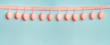 Έμβλημα ή πρότυπο Πάσχας Όμορφα ρόδινα αυγά κρητιδογραφιών που κρεμούν στην κορδέλλα στο μπλε τυρκουάζ υπόβαθρο στοκ φωτογραφία με δικαίωμα ελεύθερης χρήσης