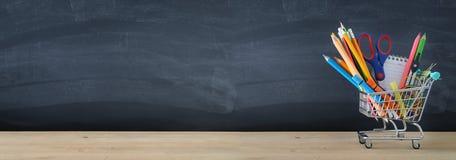 Έμβλημα του κάρρου αγορών με το σχολικό ανεφοδιασμό μπροστά από τον πίνακα πίσω σχολείο έννοιας στοκ εικόνες