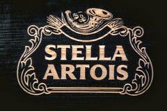 Έμβλημα της Στέλλα Artois που χαράζεται στο ξύλο, μπύρα Στοκ Εικόνες