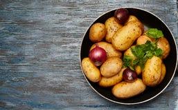 Έμβλημα τροφίμων Ακατέργαστες πατάτες, κρεμμύδια, μαϊντανός σε έναν σκοτεινό ξύλινο πίνακα στοκ εικόνες
