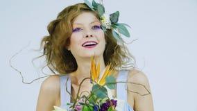 Έμπνευση άνοιξη Πορτρέτο ενός κοριτσιού με τα λουλούδια λωτού στην τρίχα της Σε μια άσπρη ανασκόπηση απόθεμα βίντεο